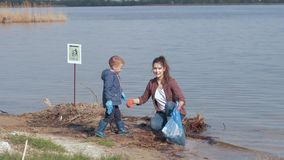 Environmental problems solutions, boy helps woman volunteer activist clean up dirty river waterfront from plastic trash. Environmental problems solutions, little stock video