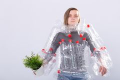 Environmental Protection, people and recyclable plastic concept - exhausted woman concerned with environment disaster. With dress as plastic bottles on white stock photo
