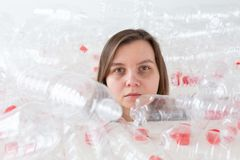 Environmental Protection, people and recyclable plastic concept - exhausted woman concerned with environment disaster. Sitting in a pile plastic bottles royalty free stock images
