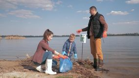 Environmental protection, woman and man volunteers with kid boy collect plastic and polyethylene trash on dirty. Environmental protection, young woman and man stock video