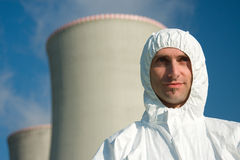 Environmental protester. Smiling environmental protester wearing white chemical suit with power station chimneys in background royalty free stock image