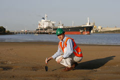 Environmental soil test. An environmental engineer, wearing protective clothing, taking a soil sample, with a beautiful blue sky behind him and a large ship stock photo