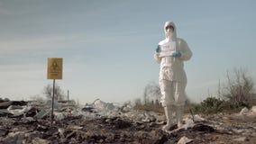 Environmentalism, mujer en traje protector y cartel de la tenencia de la máscara con lema de la contaminación de la parada en el  almacen de video