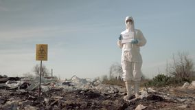 Environmentalism, woman in protective costume and mask holding poster with stop pollution slogan at landfill site with stock video
