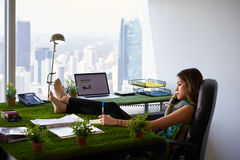 Environmentalist Woman Writes Note Barefeet On Office Desk. Concept of ecology and environment: Young business woman working in modern office with table covered Royalty Free Stock Photos