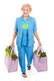 Environmentally Aware Senior Shopper. Beautiful senior lady carries her groceries in reusable cloth bags.  Full body isolated Royalty Free Stock Photo