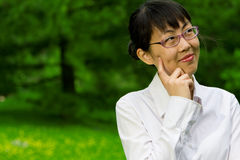 Environmentally friendly asian business woman. Outdoors in nature with green grass Royalty Free Stock Photography