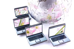 Environmentally friendly global network. Laptops around a jigsaw chrome globe reflecting flowers royalty free stock images