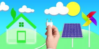 Environmentally friendly house and a hand holding a plug connected to some solar panels and windmills Stock Image