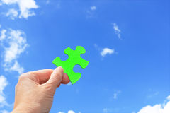 Environmentally friendly solution. Woman's hand holding green jigsaw puzzle piece against blue sky royalty free stock photography
