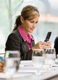 Envío de mensajes de texto de la empresaria en el teléfono celular Imagen de archivo