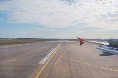 Envolez-vous la piste de vue au ciel d'aéroport et à un avion décollant dans la distance Photos stock
