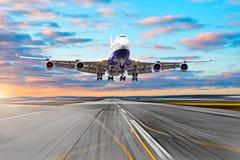 Envolez-vous la piste de vue au ciel d'aéroport et à un avion décollant dans la distance Image libre de droits