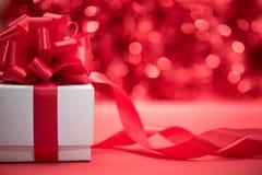 Envoltório branco da caixa de presente com curva vermelha da fita Fotografia de Stock Royalty Free