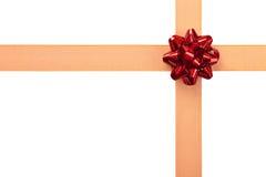 Envoltório de presente com fita alaranjada e curva vermelha Fotos de Stock Royalty Free