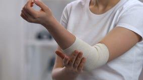 Envoltório elástico vestindo da mulher no cotovelo doloroso, problemas da artrite, doença video estoque