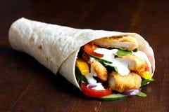 Envoltório esmigalhado da tortilha do frango frito e da salada com molho branco mim imagem de stock