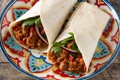 Envoltório mexicano típico do burrito com carne, frijoles e vegetais na tabela de madeira foto de stock