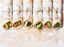 Envoltórios da tortilha com vários enchimentos na placa de madeira branca gasto foto de stock royalty free