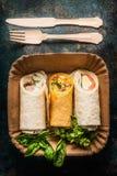 Envoltórios do vegetariano na placa de papel e na cutelaria de madeira, vista superior, fim acima imagens de stock royalty free