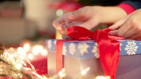 Envoltorio para regalos de la Navidad Las manos atan un regalo con una cinta roja el Nochebuena metrajes
