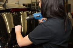 Envoltura del coche que teñe la ventana del vehículo con la hoja Foto de archivo libre de regalías
