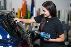 Envoltura del coche usando la pistola de calor y squegee para teñir la ventana Foto de archivo libre de regalías