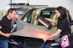 Envolturas del coche usando la lámpara de la luz roja para aplanar la película del vinilo Imágenes de archivo libres de regalías