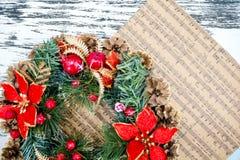 Envolva cones de abeto, conceito das músicas do Natal da partitura da preparação para os feriados, fundo de madeira gasto da tabe Imagem de Stock