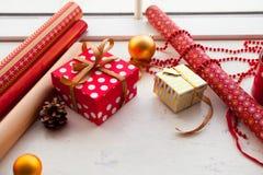 Envolviendo el regalo de la Navidad - preparación Accesorios en whi de madera Fotos de archivo libres de regalías