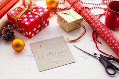 Envolviendo el regalo de la Navidad - preparación Accesorios en whi de madera Foto de archivo