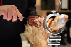 Envoyez à la boucherie découper des tranches en tranches d'un jambon espagnol de serrano Images stock