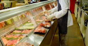 Envoyez à la boucherie s'charger de la viande enveloppée dans le réfrigérateur à la boutique 4k clips vidéos