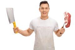 Envoyez à la boucherie tenir un fendoir et une fourchette avec un bifteck Images libres de droits