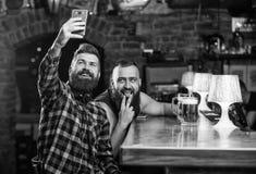 Envoyez le selfie aux r?seaux sociaux d'amis Homme en bi?re potable de barre Photo de selfie de prise pour se rappeler la grande  photographie stock libre de droits