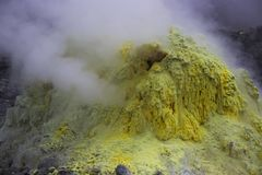 Enxofre amarelo que fuma na montanha do enxofre foto de stock