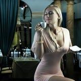 enyoing肉欲的妇女的白肤金发的咖啡 库存照片