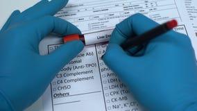 Enzima del fegato, medico che controlla nome nello spazio in bianco del laboratorio, mostrante campione di sangue in tubo video d archivio