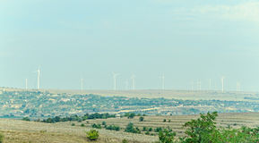 Eolian field and wind turbines farm, countryside Royalty Free Stock Photo