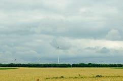 Eolian field and wind turbines farm, near yellow fllowers field, Stock Photography