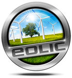 Eolic Energy - Metal Icon. Round metallic icon or symbol with wind turbines in countryside with a tree, blue sky, clouds and sun rays.  on white background Royalty Free Stock Photo