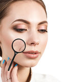 Eoman with magnifying glass showing aging skin Stock Photography