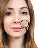 Eoman with magnifying glass showing aging skin Stock Images