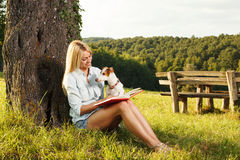 Eoman reading a book in the nature with her dog. Young woman reading a book in the nature with her dog Stock Photos