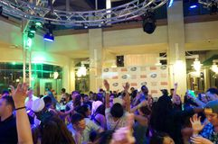 Eople dance and wave hands in air to DJ spinning music at New Years Party. Honolulu - January 1, 2016: People dance and wave hands in air to DJ spinning music at stock photos
