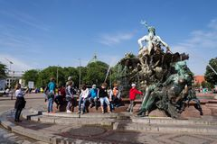 Eople in front of the Neptune fountain - Neptunbrunnen with Greek god Poseidon and woman statues in Berlin, Germany. BERLIN, GERMANY - MAY 15 2018: People in Royalty Free Stock Photos