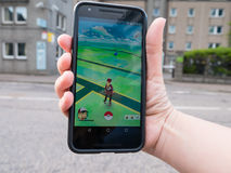 Eople playing Pokemon GO the hit augmented reality smart phone app. ABERDEEN, UNITED KINGDOM - JULY 14, 2016: People playing Pokemon GO the hit augmented reality stock photography