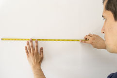 Eople pointing at a measuring tape on the wall Stock Image
