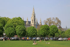 Eople relaxing in a park in Vienna near Hofburg Imperial Palace with Vienna City Hall in the background Stock Images