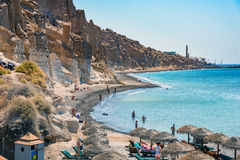 Eople swimming and sunbathing at beach near white rocks of Vlychada town of Santorini island Stock Photos